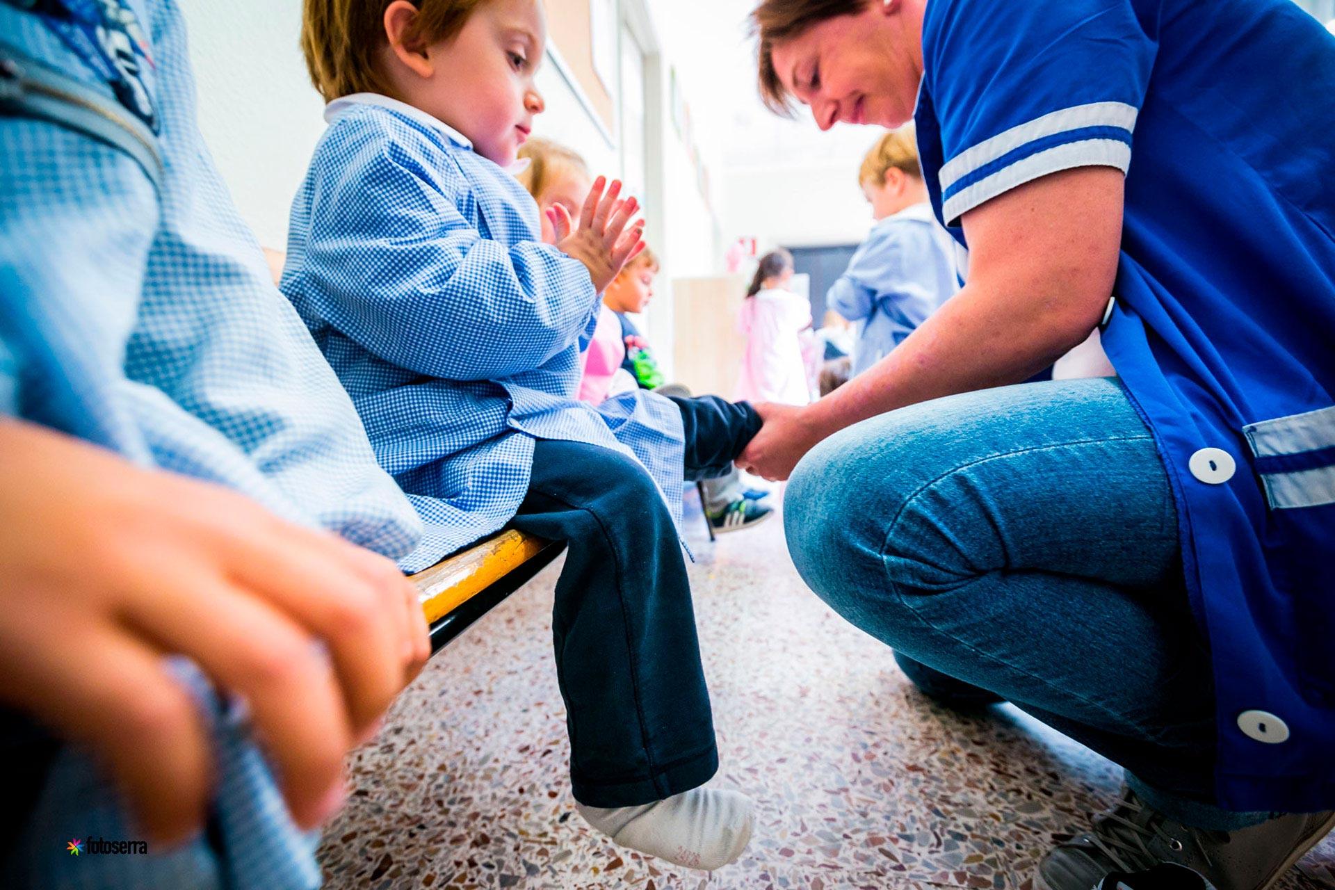 Nido del Collegio Villoresi: educatrice aiuta un bambino a vestirsi