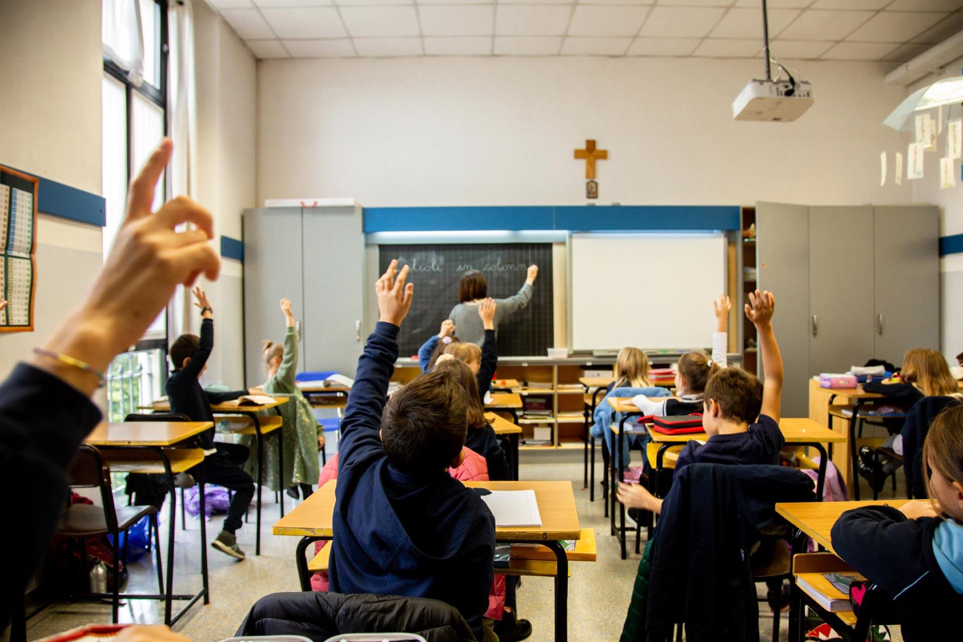 Scuola Primaria del Collegio Villoresi: bambini con la mano alzata in classe